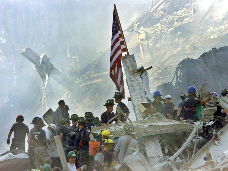 Die US-Flagge wird am Tag nach dem Anschlag auf den Trümmern der eingestürzten Twin Towers gehisst. Foto: Beth A. Keiser / Pool/AP POOL/EPA FILE/dpa
