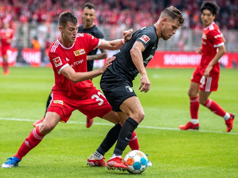 Augsburgs Florian Niederlechner (r) schirmt den Ball gegen den Unioner Robin Knoche ab. Foto: Andreas Gora/dpa