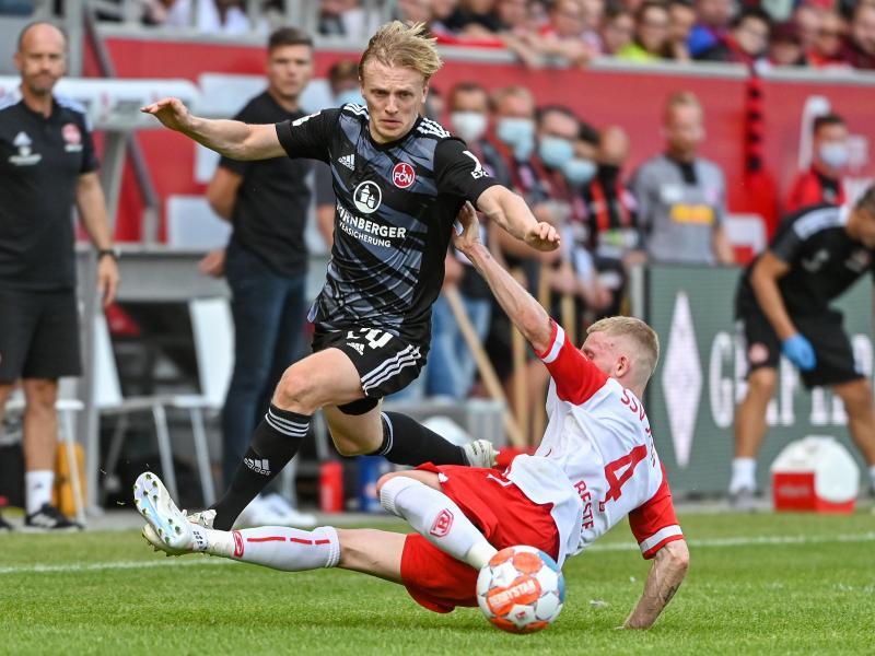 Jan-Niklas Beste musste sich mit Spitzenreiter Regensburg (r) mit einenPunkt gegen den 1. FC Nürnberg zufrieden geben. Foto: Armin Weigel/dpa