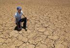Ein Landwirt kniet auf dem Boden eines ausgetrockneten Wasserlochs in Südafrika. Foto: Denis Farrell/AP/dpa