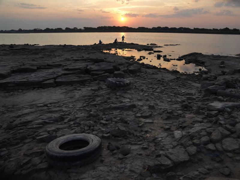 Menschen angeln am Ufer des Paraguay-Flusses. Durch die Dürre im paraguayisch-brasilianischen Pantanalgebiet drohen Rekordtiefstände - wie schon im vergangenen Jahr. Foto: Jorge Saenz/AP/dpa