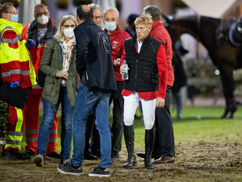 Marcus Ehning (2.v.r) steht nach seinem Sturz neben Sanitätern und Ärzten und Bundestrainer Otto Becker (r). Foto: Rolf Vennenbernd/dpa