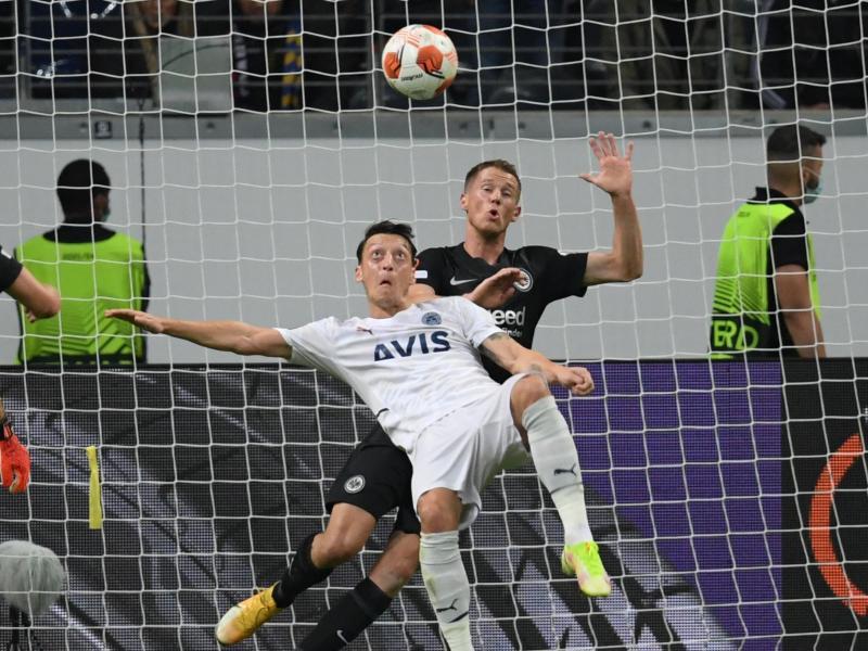 Frankfurts Erik Durm (r) und Istanbuls Mesut Özil kämpfen um den Ball. Foto: Arne Dedert/dpa