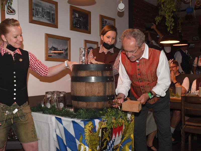 Zwei Schläge braucht Christian Ude beim Fassanstich im Schiller Bräu. Foto: Felix Hörhager/dpa