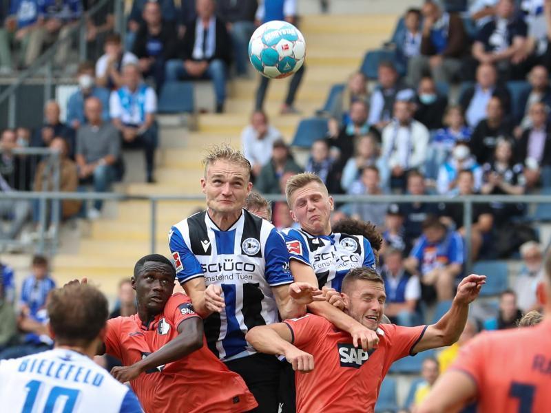 Bielefelds Amos Pieper (oben, l) setzt sich im Kopfballduell gegen Hoffenheims Diadie Samassekou (unten, l-r) und Pavel Kaderabek durch. Foto: Friso Gentsch/dpa