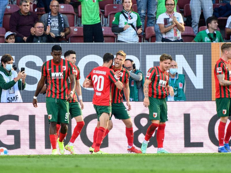 Augsburgs Torschütze Florian Niederlechner (M) jubelt mit seiner Mannschaft über den Treffer zum 1:0. Foto: Matthias Balk/dpa