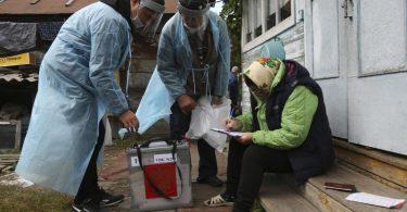 Zwei Wahlhelfer stehen neben einer Frau, die auf den Stufen vor einem Haus sitzt und Dokumente ausfüllt. Foto: Evgeniy Sofiychuk/AP/dpa