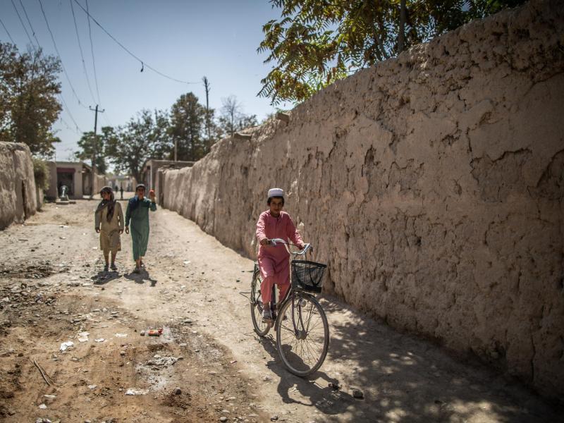 Ein afghanischer Junge fährt in Isa Khel außerhalb von Kundus Fahrrad. Foto: Oliver Weiken/dpa