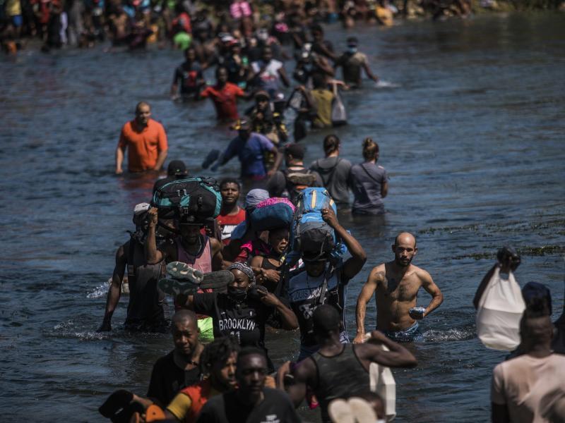 Migranten waten durch den Rio Grande und hoffen auf Zuflucht in den USA. Doch das Land gibt sich hart und setzt auf Massenabschiebungen. Foto: Felix Marquez/AP/dpa
