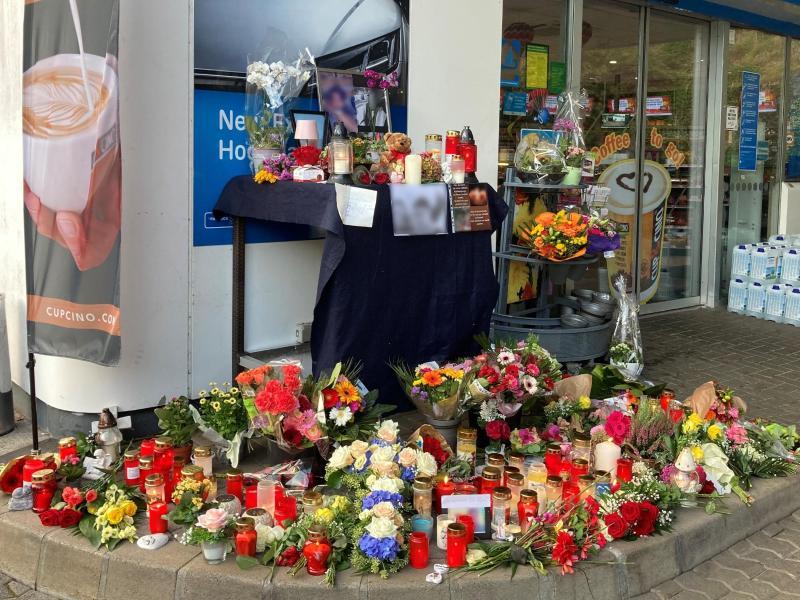 Menschen haben Blumen und Kerzen am Tatort abgelegt. Foto: Birgit Reichert/dpa