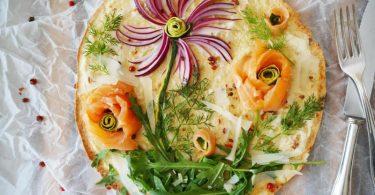 Kreativer Pizza-Belag: Mit roten Zwiebelstreifen, Rucola und Dill sowie Lachs- und Zucchini-Röschen entsteht im Handumdrehen eine Blumenwiese zum Essen. Foto: Doreen Hassek/hauptstadtkueche.blogspot.com/dpa-tmn