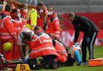 Mediziner versorgen Linienrichterin Helen Byrne, das Spiel ist unterbrochen. Foto: Hendrik Schmidt/dpa-Zentralbild/dpa