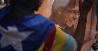Ein Mann hält ein bedrucktes Tuch mit dem Bild des ehemaligen katalanischen Regierungschefs Puigdemont während eines Protests vor dem italienischen Konsulat in Barcelona. Foto: Joan Mateu/AP/dpa