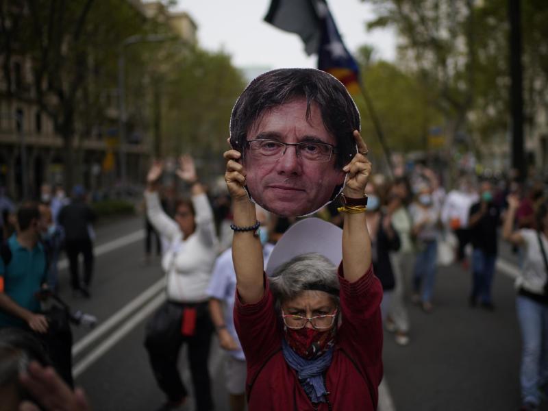 Eine Frau hält einen aus Pappe ausgeschnittenen Kopf des ehemaligen katalanischen Regierungschefs Puigdemont während einer Demonstration in Barcelona in die Höhe. Foto: Joan Mateu/AP/dpa
