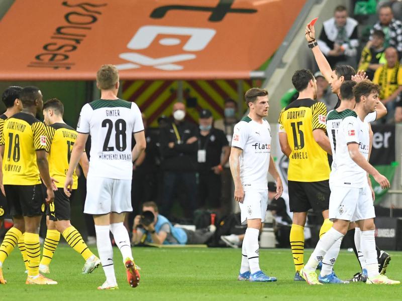 Schiedsrichter Deniz Aytekin (3.v.r) stellt Dortmunds Mahmoud Dahoud (l) vom Platz. Foto: Bernd Thissen/dpa