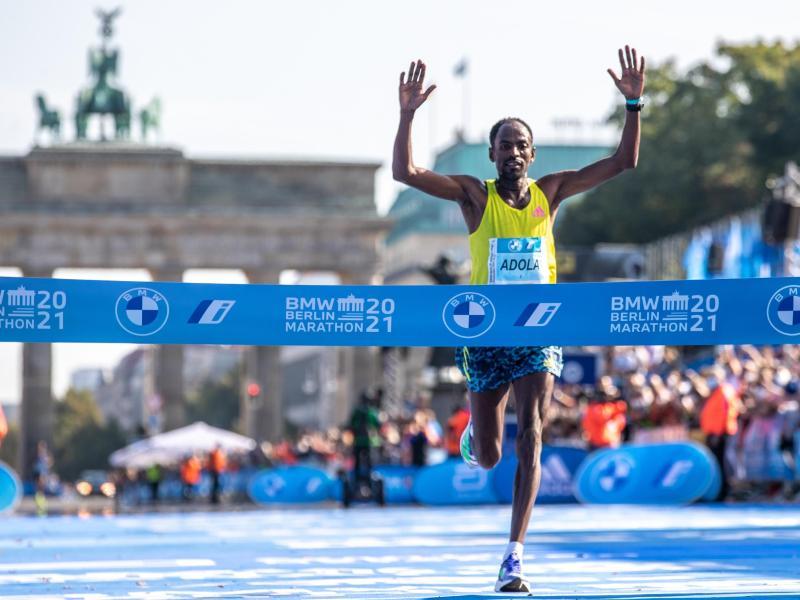 Guye Adola aus Äthiopien läuft beim Berlin Marathon nach 2:05:45 Stunden als Erster durchs Ziel. Foto: Andreas Gora/dpa