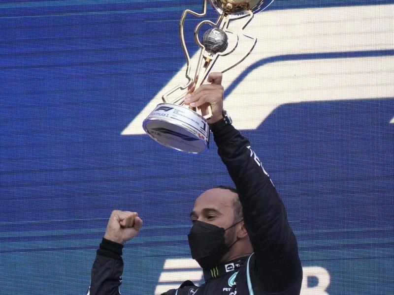 Weltmeister Lewis Hamilton mit der Siegertrophäe. Foto: Sergei Grits/AP/dpa