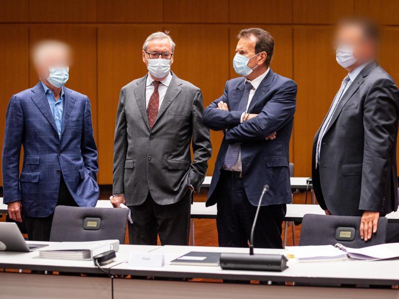 Horst Neumann (2.v.l) und Karlheinz Blessing (2.v.r), ehemalige VW-Konzernpersonalvorstände, stehen mit zwei weiteren Angeklagten kurz vor Prozessauftakt in der Stadthalle Braunschweig zusammen. (Archivbild). Foto: Moritz Frankenberg/dpa