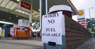 """Ein Zettel mit der Aufschrift """"Entschuldigung, kein Benzin verfügbar"""" an einer Tankstelle im englischen Bracknell. Foto: Steve Parsons/PA/dpa"""