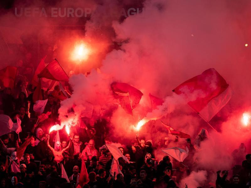 Antwerpen-Fans schwenken vor der Partie Bengalos. Foto: Marius Becker/dpa