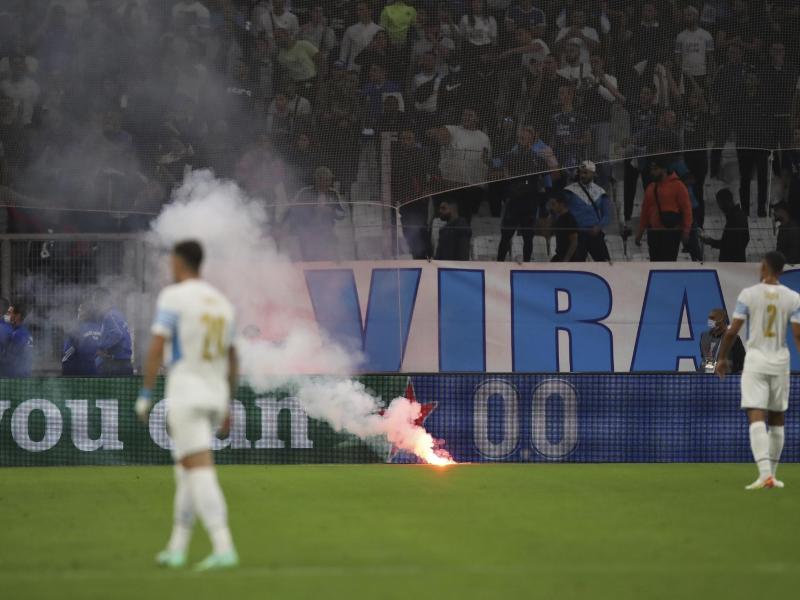 Es wurden auch Feuerwerkskörper auf Fans geschleudert. Andere Brandobjekte erreichten das Spielfeld. Foto: Daniel Cole/AP/dpa