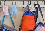 Masken hängen zusammen mit Taschen und Rucksäcken an Kleiderhaken in einem Klassenraum einer Grundschule. (Archivbild). Foto: Patrick Pleul/dpa-Zentralbild/dpa