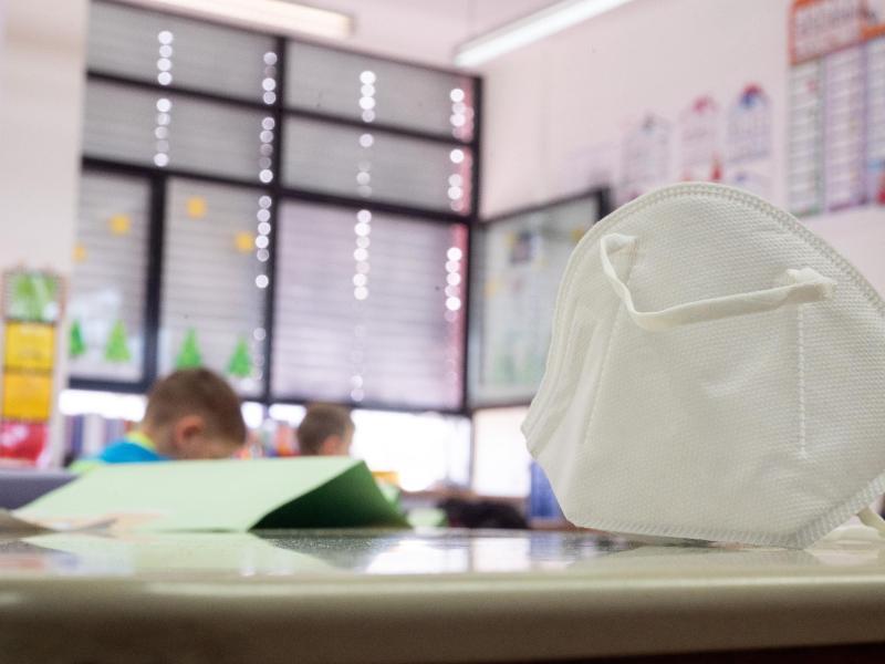 Eine FFP2-Maske liegt in einer Grundschule auf einem Tisch. In zwei Bundesländern greifen ab Montag Lockerungen bei der Maskenpflicht an Schulen. Foto: Sebastian Gollnow/dpa
