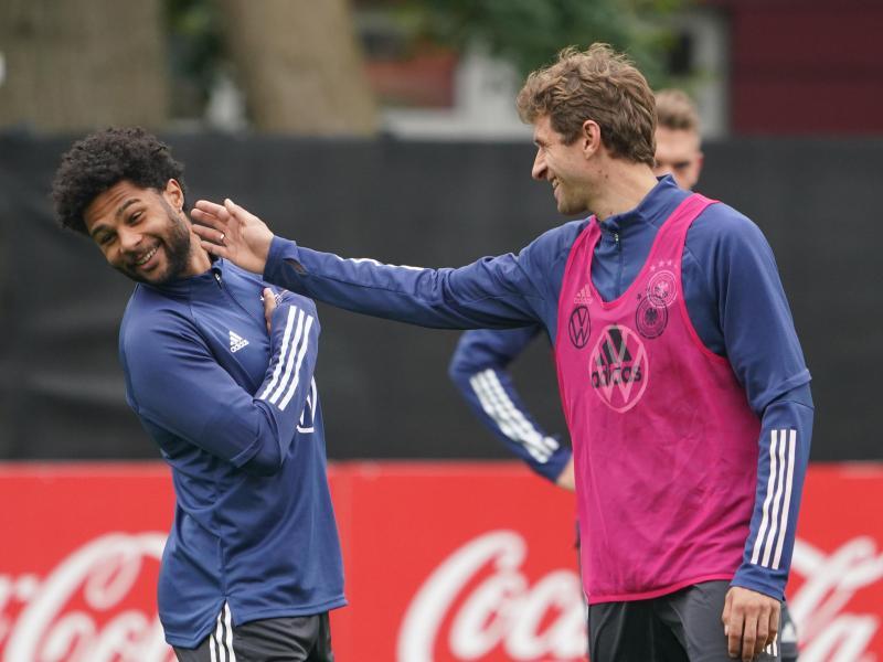 Thomas Müller (r) schertzt im Training mit Serge Gnabry. Foto: Marcus Brandt/dpa