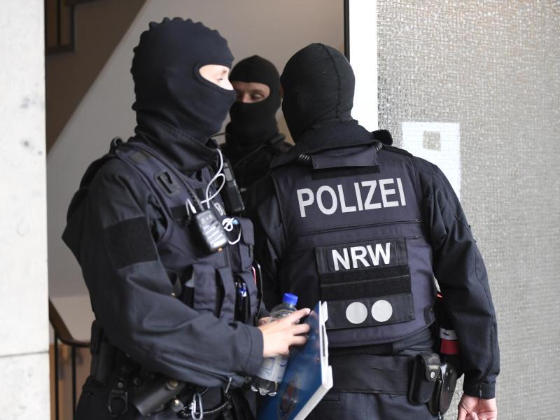 Polizisten durchsuchen ein Gebäude in Düsseldorf beim landesweiten Polizeieinsatz gegen Geldwäsche und Terrorfinanzierung. Foto: Roberto Pfeil/dp/dpa