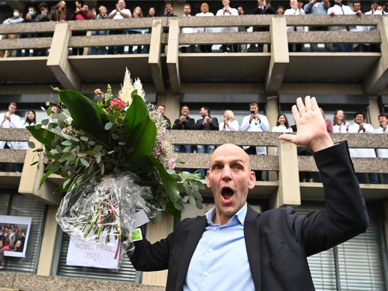 Benjamin List freut sich mit einem Blumenstrauß bei der Ankunft am Max-Planck-Institut (MPI) für Kohlenforschung. Foto: Federico Gambarini/dpa