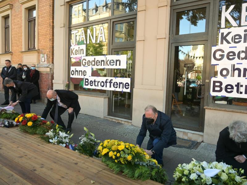 Halles Bürgermeister Egbert Geier (SPD, l) und Sachsen-Anhalts Ministerpräsident Reiner Haseloff (CDU, M) legen vor einem der Tatorte, einemDöner-Imbiss, Kränze für die Opfer des Anschlags vor zwei Jahren nieder. Foto: Heiko Rebsch/dpa / Zentralbild/dpa