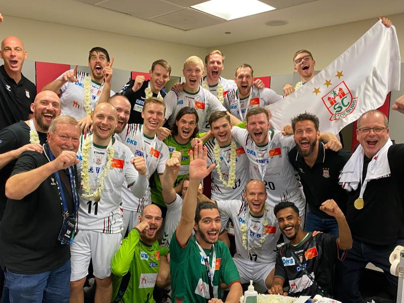 Die Mannschaft des SC Magdeburg jubelt über den Sieg im Finale des IHF Super Globe in Saudi Arabien gegen den FC Barcelona. Foto: -/SC Magdeburg/dpa