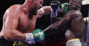 Tyson Fury (l) kann am Kopf von Deontay Wilder einen Treffer landen. Foto: Chase Stevens/FR171365 AP/dpa
