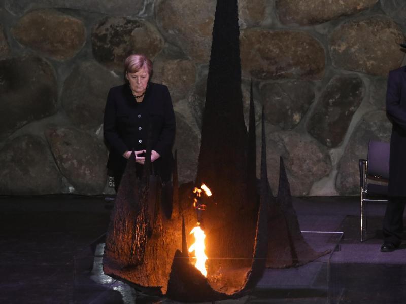 Angela Merkel steht an der Ewigen Flamme in der Halle der Erinnerung der Holocaust-Gedenkstätte Yad Vashem. Foto: Ariel Schalit/AP/dpa