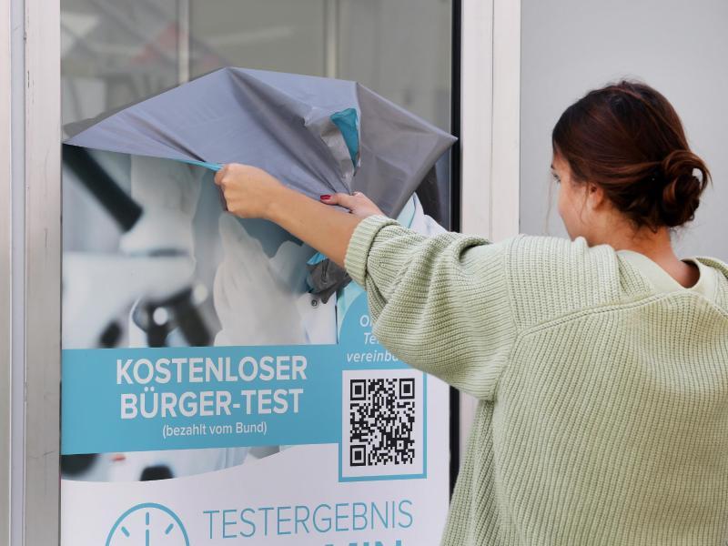 Die Werbeaufkleber eines Corona-Testlabors werden von einer Mitarbeiterin entfernt. (Archivbild). Foto: Roland Weihrauch/dpa