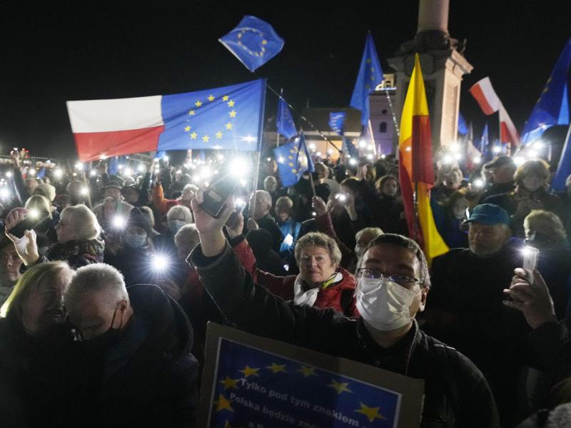Menschen halten während einer Demonstration in Warschau die Taschenlampen ihrer Mobiltelefone hoch. Foto: Czarek Sokolowski/AP/dpa