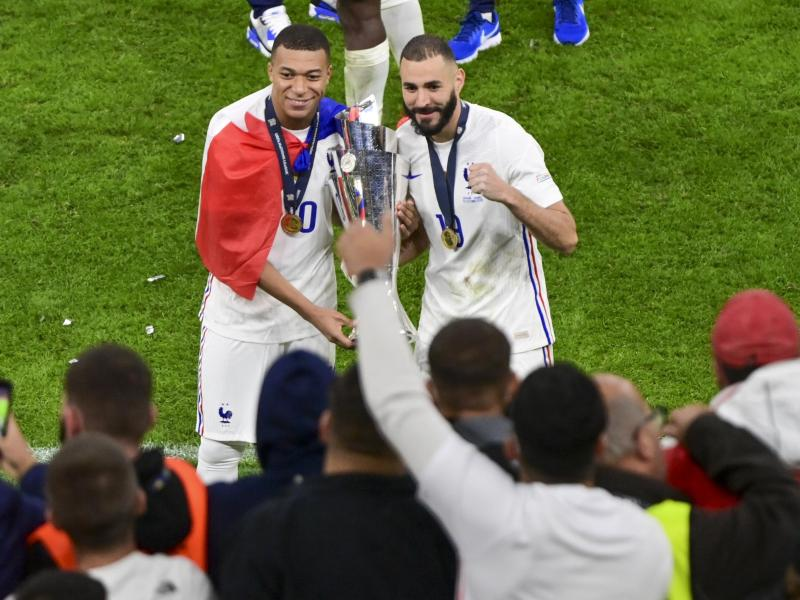 Kylian Mbappé (l) und Karim Benzema feiern den Gewinn der Nations League. Foto: Miguel Medina/Pool AFP via AP/dpa