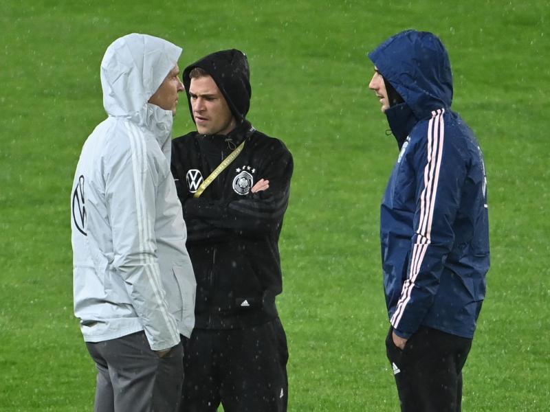 Oliver Bierhoff (l-r), Direktor Nationalmannschaften und Akademie, spricht mit Joshua Kimmich und Leon Goretzka vor dem Spiel auf dem Rasen. Foto: Federico Gambarini/dpa