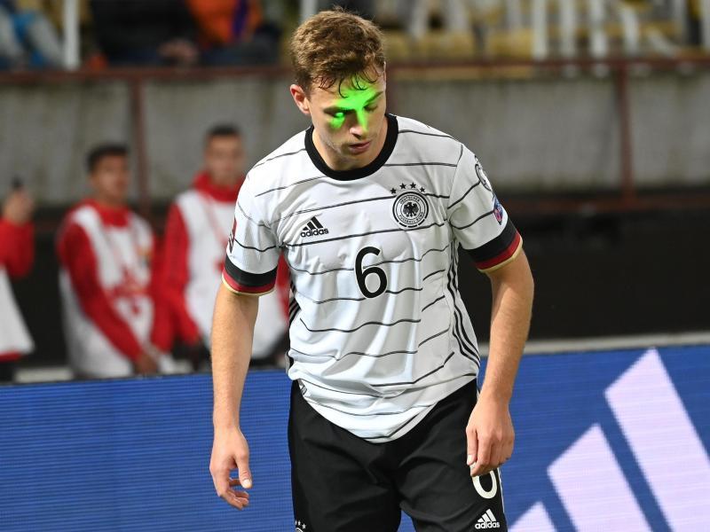 Deutschlands Joshua Kimmich wird während der Partie von einem Laserpointer geblendet. Foto: Federico Gambarini/dpa