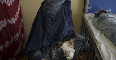 Eine Frau hält eines ihrer beiden Babys, die in Kabul behandelt werden, auf dem Arm. Foto: Felipe Dana/AP/dpa