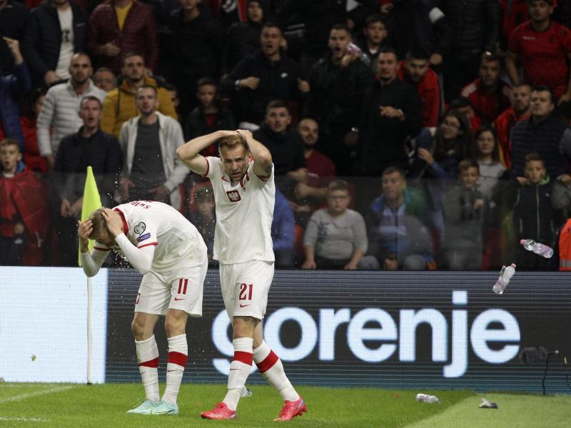 Polen Spieler schützen sich vor den Flaschenwürfen der albanischen Anhänger. Foto: Franc Zhurda/AP/dpa