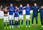 Schalkes Spieler feiern den Last-Minute-Sieg in Hannover vor ihren mitgereisten Fans. Foto: Julian Stratenschulte/dpa