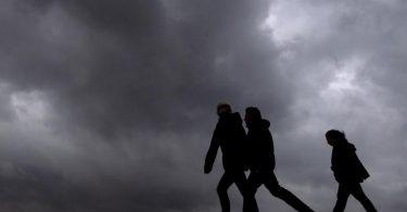 Strand-Spaziergänger unter dunklen Wolken. Foto: Sina Schuldt/dpa