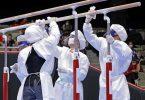 Mitglieder des Organisationsteams desinfizieren in Schutzanzügen und mit Mund-Nasen-Schutz die Geräte. Foto: -/kyodo/dpa/Archivbild