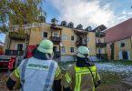 Feuerwehrmänner stehen vor einem ausgebrannten Mehrfamilienhaus. Foto: Armin Weigel/dpa