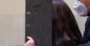 Will nicht gefilmt und fotografiert werden: Die Angeklagte Jennifer W. mit einem Ordner vor dem Gesicht. Foto: Sven Hoppe/dpa