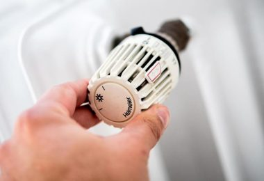 Ein Mann dreht am Thermostat einer Heizung. Foto: Hauke-Christian Dittrich/dpa